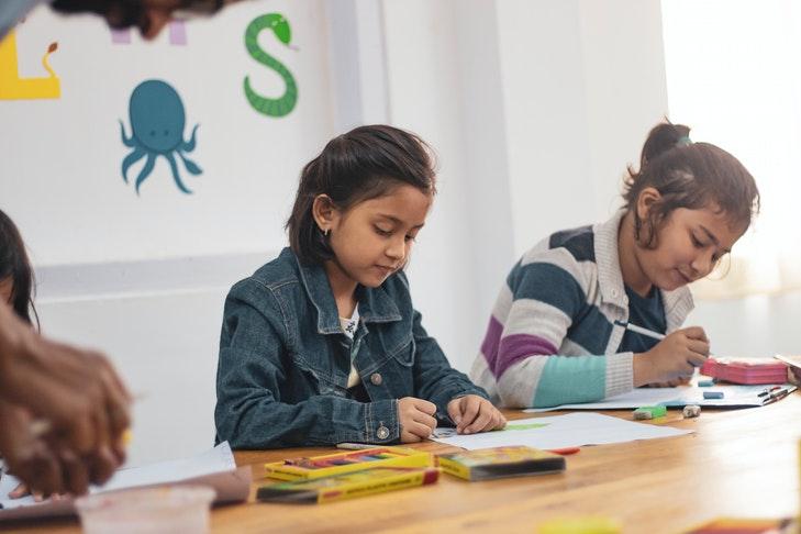 Zwei Mädchen zeichnen in einem Klassenraum.
