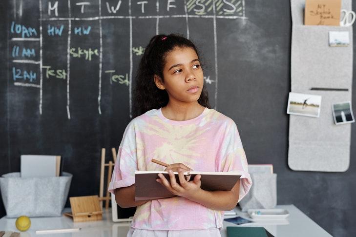 Ein Mädchen steht vor einer Tafel mit einem Zeichenblock und schaut nachdenklich zur Seite.