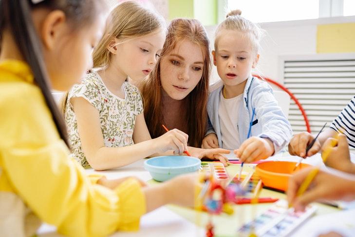 Eine Lehrerin schaut zwei Schülerinnen beim Malen mit einem Tuschkasten zu.