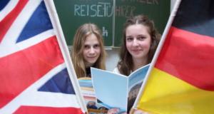 Auf dem Bild sind zwei Mädchen, die zwischen einer britischen und einer deutschen Flagge stehen und einen Reiseführer in der Hand halten. Die Schüler und Schülerinnen des Humanistischen Greifenstein Gymnasiums erstellten einen Reiseführer für die Stadt Thum.
