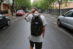 Ein Schüler hält sich am Kopf und läuft alleine auf der Strasse. Wir sagen dir jetzt, was Mobbing ist und welche Arten von Mobbing es gibt.