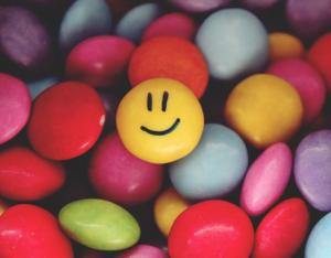 Auf dem Bild sind viele bunte Smarties zu sehen, auf einem gelben ist ein Smiley-Gesicht zu sehen. Du erfährst jetzt, wie man das Kennenlernspiel Flower Power durchführt.