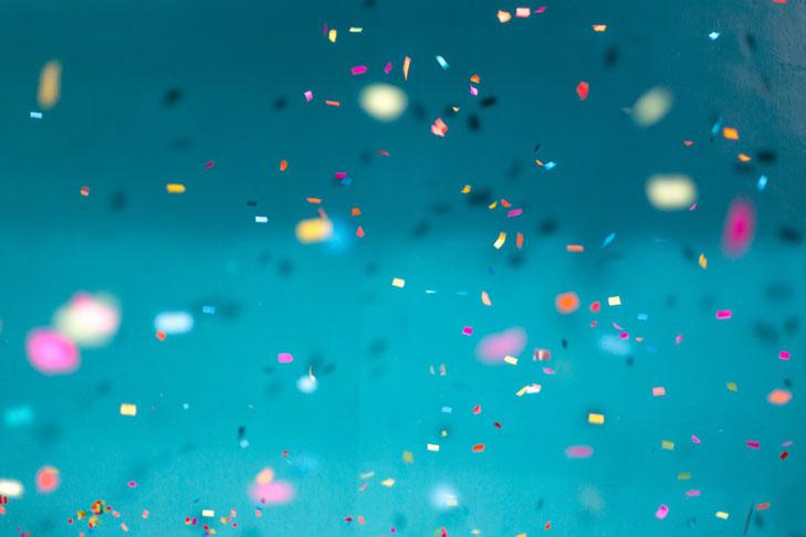 Konfetti fliegt vor einem blauen Hintergrund in die Luft.