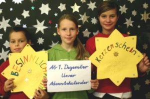 Drei Kinder stehen vor einer Sternenwand und präsentieren einen Adventskalender. Die Schüler und Schülerinnen können sich Rezepte, Geschichten, Bastelideen überlegen und so einen Wissenskarten-Adventskalender gestalten.