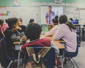 Ein Lehrer steht im Klassenzimmer und unterrichtet Schüler und Schülerinnen. Jetzt befassen wir uns mit Regeln für hilfreiches Feedback.