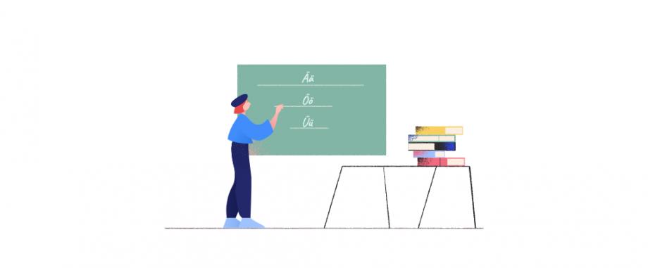 Eine Lehrerin steht im Klassenzimmer und schreibt die Buchstaben Ä, Ö und Ü an die Tafel. In diesem Post findest du Unterrichtsmaterialien zum Thema Umlaute.