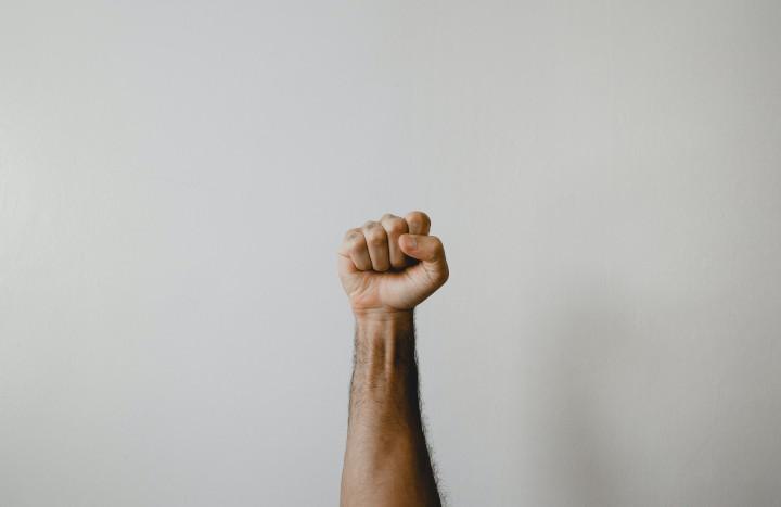 Eine gereckte Faust vor einer weißen Wand symbolisiert das Gleichheitsideal unserer Gesellschaft. Denn der Begriff Soziale Ungleichheit ergibt nur Sinn, wenn dieses Gleichheitsideal besteht.