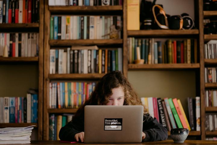 Ein Mädchen sitzt zuhause an einem Laptop vor einem großen Bücherregal. Wer aus einem Haushalt mit hohem Bildungsgrad kommt, hat es beim Homeschooling wesentlich leichter, was soziale Ungleichheit verstärkt.
