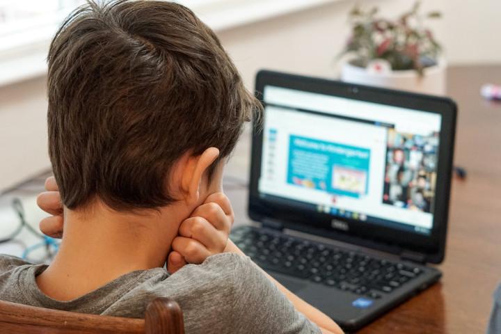Ein Junge sitzt vor einem Laptop und soll sich mit digitalem Lernen beschäftigen. Für viele Schülerinnen und Schüler ist das ein Problem, weil zuhause die Lernbedingungen nicht stimmen.