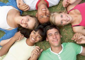 Fünf Jugendliche liegen auf einer Wiese und halten sich an den Händen. Speaking Cards sind optimal für Freiarbeit geeignet, denn sie nehmen den Schülern und Schülerinnen die Angst vor alltäglichen Gesprächen in einer Fremdsprache.