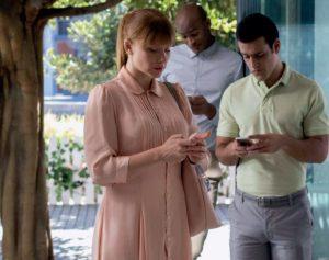 Zwei Männer und eine Frau schauen auf das Display ihres Handys. Es ist wichtig, dass Schülerinnen und Schüler lernen, Informationen aus dem Internet kritisch zu hinterfragen und sich Gedanken darüber machen, was sie alles online von sich preisgeben
