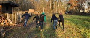 Gruppe vin fünf rennenden Schülern