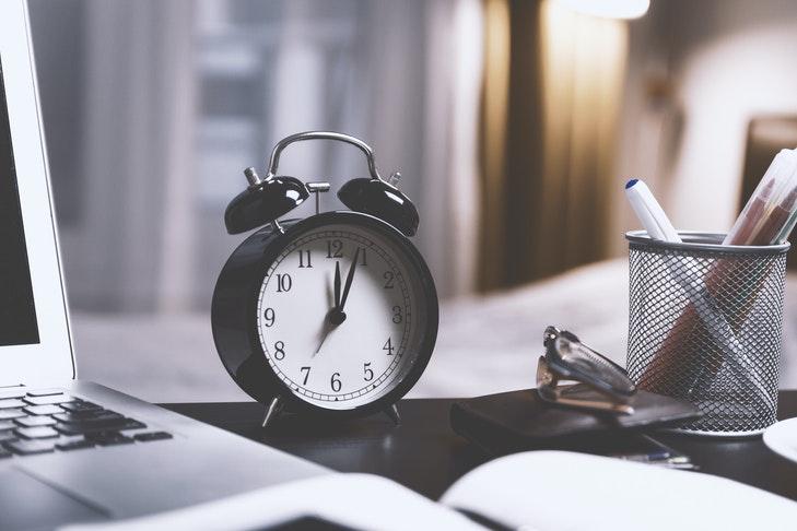 Ein Wecker steht auf einem Schreibtisch zwischen einem Laptop und einem Behälter mit Stiften. Sich klare Zeitvorgaben zu setzen, hilft beim Korrigieren ungemein. In diesem Abschnitt zeigen wir dir, wie du vorgehen kannst.