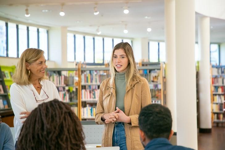 Eine junge Frau steht im Foyer einer Bibliothek neben einer älteren Dame und spricht zu mehreren Menschen. Der Austausch mit deinen Lehrerkolleginnen und Kollegen ist extrem wichtig, wenn du deinen Korrekturprozess angenehmer gestalten möchtest.