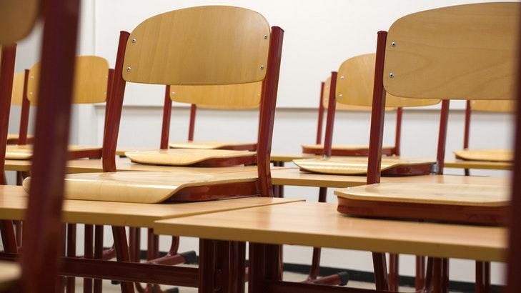 Stühle stehen in einem Klassenzimmer hochgeräumt auf den Tischen. Ruhigere Zeiten im Schulbetrieb wie Freistunden kannst du auch für Korrekturen nutzen, statt mit den Kollegen und Kolleginnen Kaffee zu trinken.