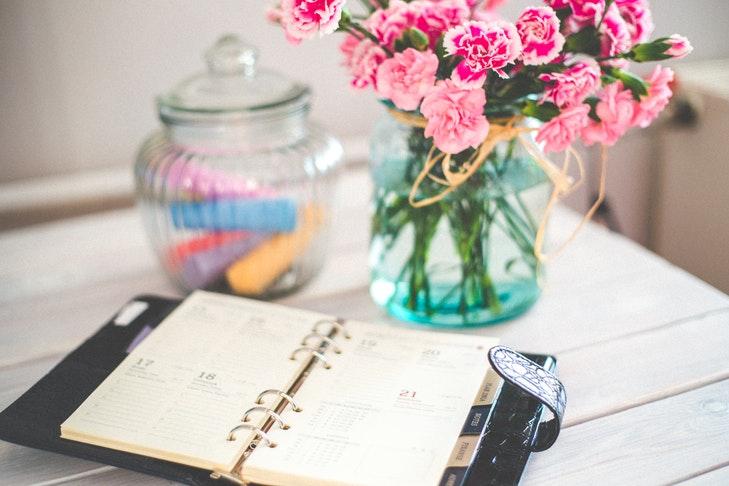 Ein Kalender liegt auf einem Holztisch, dahinter steht eine Blumenvase. Einen Korrigierkalender zu führen, ist sehr hilfreich, wenn du deinen Korrekturprozess besser organisieren möchtest. Wir geben dir praktische Tipps dafür.