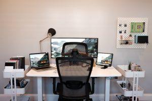 Ein modern eingerichtetes Arbeitszimmer mit Schreibtisch, Computer und Schreibmaterial. Es ist wichtig, dass deine beruflichen Tätigkeiten wie die Vorbereitung oder das Lesen von Mails nur im Arbeitszimmer stattfinden. Somit kannst du nämlich auch deine Arbeitsbelastung reduzieren.