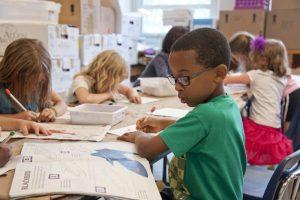 Schüler und Schülerinnen sitzen im Klassenzimmer und schreiben in ihre Hefte. Lass im Unterricht deine Klasse aktiver sein und mehr zu Wort kommen. So kannst du schnell deine Arbeitsbelastung reduzieren