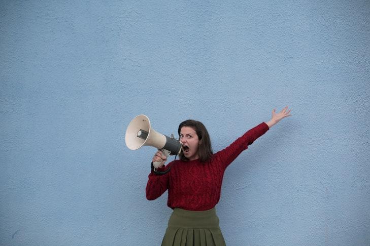 Eine Frau in einem roten Pullover steht mit einem Megaphon vor einer blauen Wand. Die eigene Stimme richtig einzusetzen, ist für Lehrerinnen und Lehrer eine essentielle Fähigkeit. In unserem Beitrag erklären wir dir, wie du deiner Stimme etwas Gutes tun kannst.