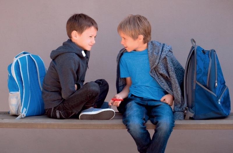 Zwei Jungs sitzen auf eine Bank und reden. Mit dem E-Book des Friedrich Verlags lernen Kinder in der Grundschule aktiv zuzuhören, was eine Kernkomponente der gewaltfreien Kommunikation darstellt.