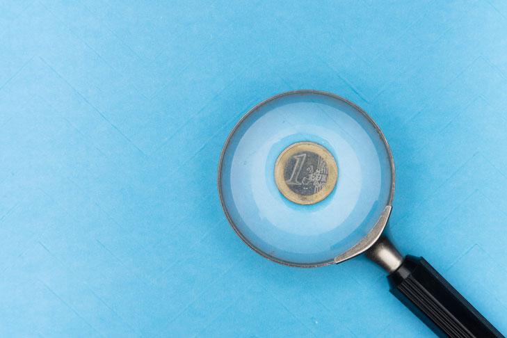 Ein 1-Euro-Stück unter eine Lupe ist vor einem blauen Hintergrund zu sehen. Lehrkräfte in Deutschland sind im internationalen Vergleich gut bezahlt. Allerdings gibt es Unterschiede je nach Schulform. Welche das sind, erfährst du im nun folgenden Kapitel.
