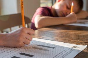 Zwei Schüler schreiben einen Test. Jetzt erfährst du, was LehrerInnen machen können, um den Schülern und Schülerinnen das Spicken zu erschweren.