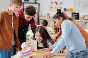 Schüler und Schülerinnen sind im Klassenzimmer und schauen auf ein Smartphone.