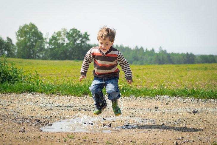 Ein Junge springt in einer Matschpfütze umher.