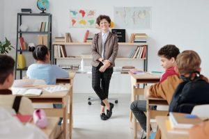 Eine Lehrerin steht vor den Schülern und Schülerinnen und lacht.